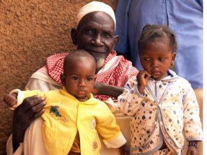 Grandfather with children in Niger 2009. The children's mom bled to death when they were born.